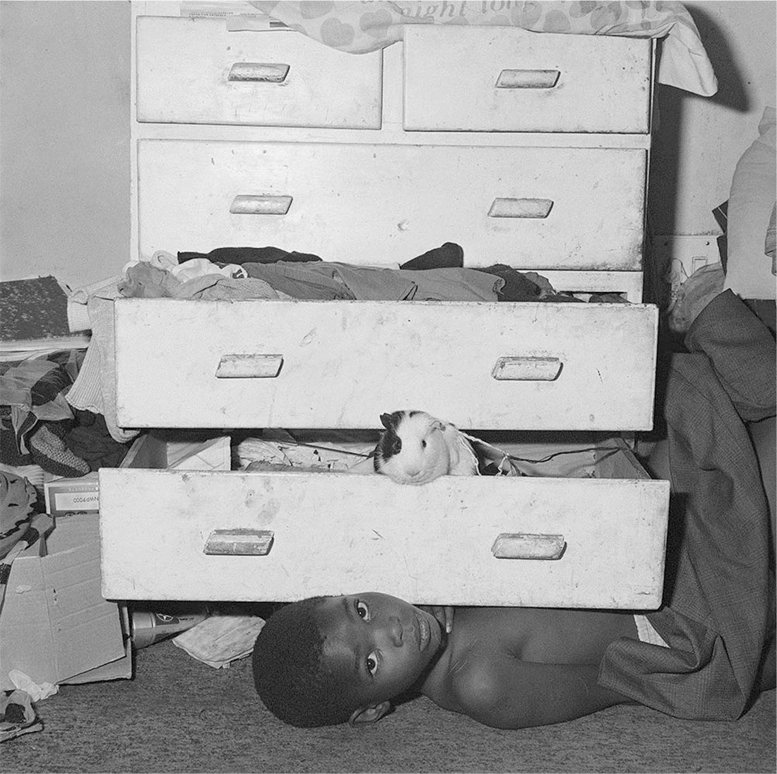 Roger-Ballen-Outland-Unpublished-Child-under-chest-of-drawers-2000